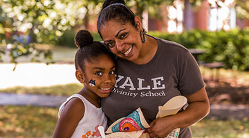 A mom wearing a Yale divinity school shirt hugging daughter
