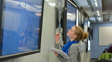 A student looks at her research on a large computer screen