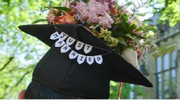Student from commencement wearing decorated cap displaying the words just married