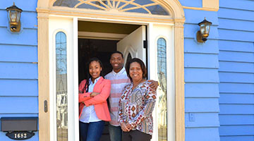 New Haven homebuyer particpant Wendy Hall standing with her family in their new home