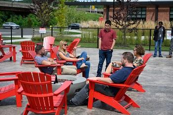 Staff networking in the outdoor lounge area at the IT summer picnic