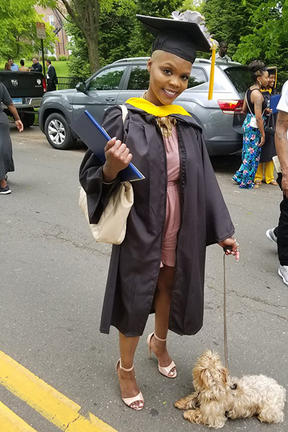 Picture of Sharees Mcleod in her graduation gown with dog at her feet