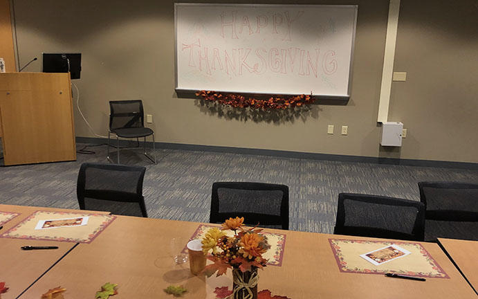 Tables setup with holiday decor and supplies for writing what staff are thankful for.