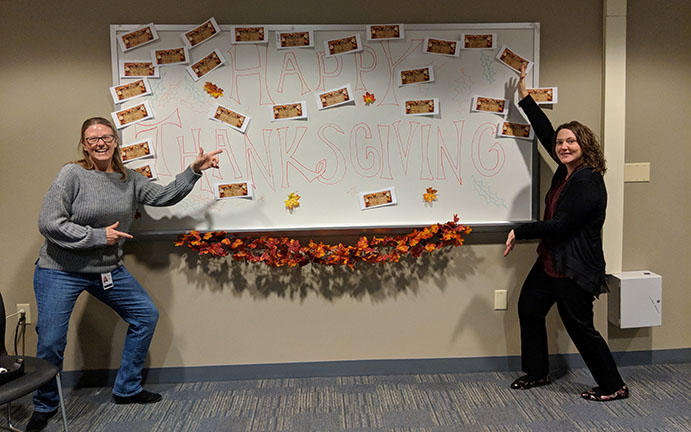 "Chloe Kennedy Turnbull (left) and Cynthia Welsh (right) displaying the ""Wall of Thanks""."